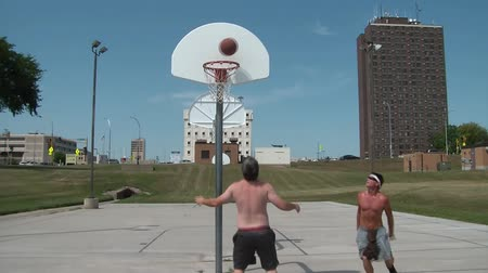 стрельба : Two men play one on one basketball in sunshine with urban backdrop. Стоковые видеозаписи