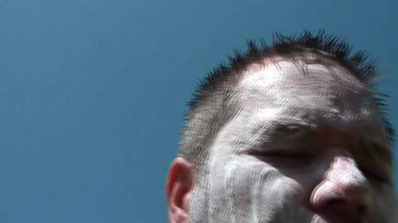 kapatmak : Man washes face with white soap, hoses off at end, with full blue sky as a background. Stok Video