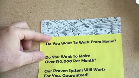 garça real : Hand pins up a yellow work from home flyer that asks whether reader wants to make over $10,000 per month. Stock Footage