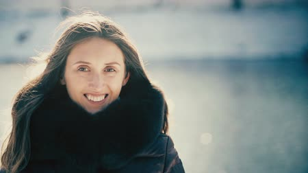 мороз : Happy Romantic Girl Looking at Camera in Snowy Park. Candid Portrait of Smiling Woman Outdoors in Winter. Sunlight. Windy Weather. Snow, Water and Beautiful Bokeh Background. Backlit.