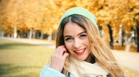шляпа : Young Fashion Hipster Girl in Sunny Autumn Day. Candid Smiling Happy Female Looking at Camera. Close-Up Trendy Casual Woman Portrait. Wind Waving Her Hair. Tree in Fall Background. Toned Footage. Стоковые видеозаписи