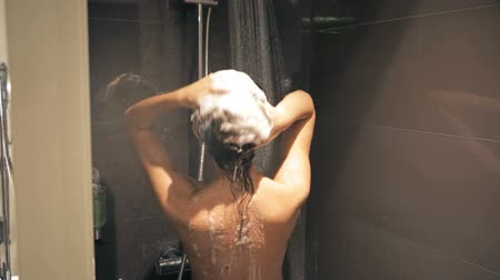 wanna : Beautiful Young Slim Woman Taking a Shower and Washing Hair with Shampoo. Slender Girl Enjoying a Shower. Body Care in Douche Concept. Brown Background.