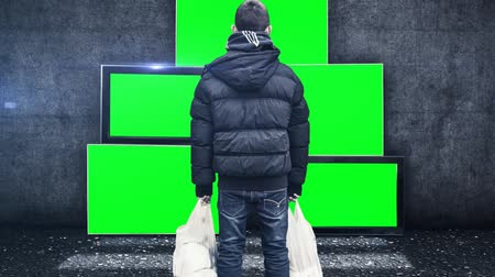 tv screen : a young boy stays in front of tv screens and looking to the tv green screen