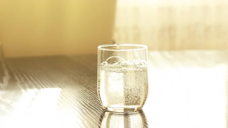 cristalino : Pouring mineral water in the glass at the kitchen in the shining sunlight weather