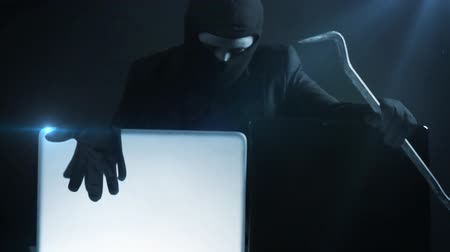 кража : computer hacker in suit stealing data from laptop with crowbar