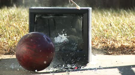 low lighting : An old analog television is destroyed with a make-shift wrecking ball made from rope and a bowling ball.  Shot at 60fps and re-interpreted at 24fps for slow motion.
