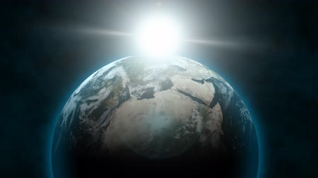 солнечный : From outer space, planet Earth rotates with a blue atmospheric glow as the sun rises behind it.  The clouds in the Earths atmosphere are also animated.  Also available in:  [link]stock-footage290910 [item]290910 iconsres[item][link] 24fps for FILM  [