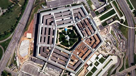 терроризм : A slow aerial zoom in on the United States Pentagon building in Arlington, Virginia, shot from a satellite perspective above. Realistic animation with moving cloud shadows and traffic on the streets and freeways.