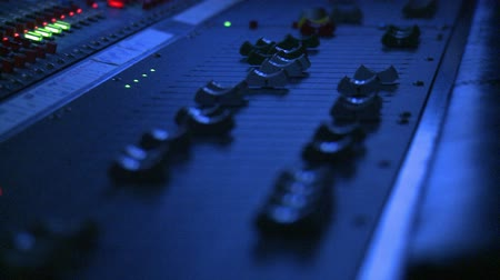 mikser : Floating close up on the fader controls of a professional sound mixing board.