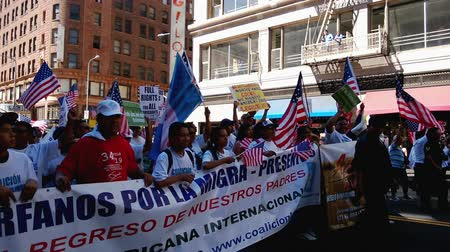 rali : People Marching at Immigration Rally. Hundreds of people young and old march while waving picket signs and American flags in the air using noise makers and cheer during an immigration rally in downtown Los Angeles on September 22 2013.