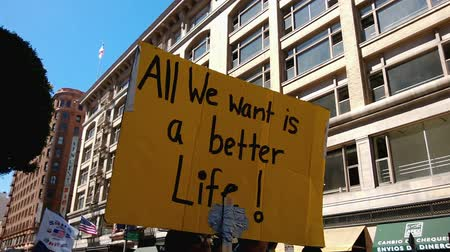 rali : A Better Life Rally Sign. A large yellow picket sign that reads All We Want Is A Better Life is held up during an immigration rally in downtown Los Angeles on September 22 2013.