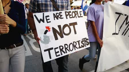 illegal alien : We Are People Not Terrorists Rally Sign. A white picket sign that reads We Are People Not Terrorists is held up during an immigration rally in downtown Los Angeles on September 22 2013. Stock Footage