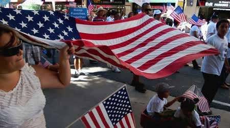 illegal alien : Family Waving American Flag Banner. Among hundreds of small American flags people wave in their hands one family displays a large flag as a banner during an immigration rally in downtown Los Angeles on September 22 2013.