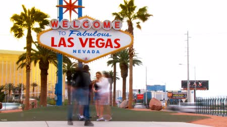 tiras : Timelapse wide shot of the world famous Welcome to Fabulous Las Vegas Nevada sign with tourists walking around and in front of the landmark posing for pictures with traffic passing by in the background. Designed in the MidCentury modern architecture sty Stock Footage