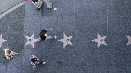 solo : Hollywood Walk of Fame from Above. Looking straight down on the sidewalk, people pass underneath the camera as they walk along the stars from the world famous Hollywood Walk of Fame. Stock Footage