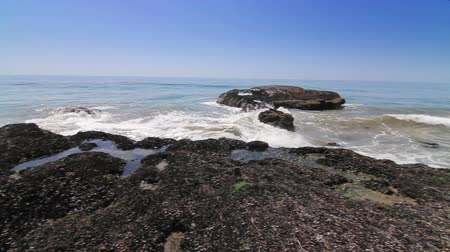 kullancs : Surfs Up Malibu, Slow Pan. Slow camera pan as waves crash onto barnacle covered rocks, spewing ocean water into the air and flooding the rocks below.