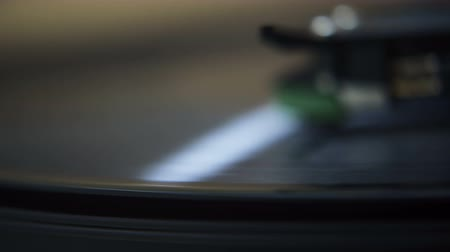 dengeleme : Macro Record Player Spin. Macro close up on the edge of a spinning vinyl as a stylus drops onto the record.