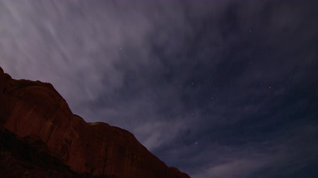 земной : Star Tracking Time-lapse. Clouds passing over a mesa in Utahs scenic Monument Valley revealing the night sky with dozens of stars. Orions Belt and Mars are among the celestial bodies visible in this shot. Стоковые видеозаписи