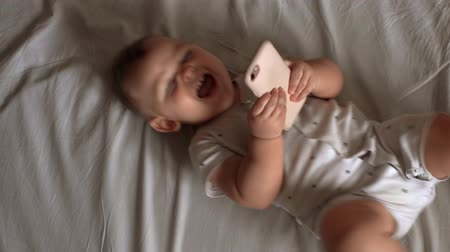 невинный : Little cute baby is lying on the bed, jerking legs and playing the smartphone Стоковые видеозаписи