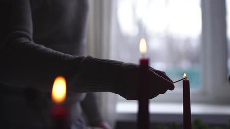 панорамирования : Male hand on the background of the window lights candles in slow motion
