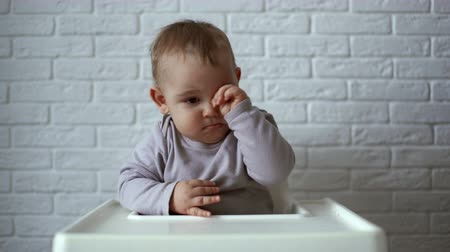 rubs : Little cute boy rubs his eyes while sitting in a childrens chair Stock Footage