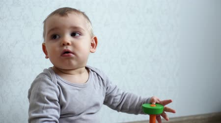 невинный : Little cute baby wary looks around and holding child pyramid in his hand