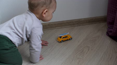 nevinný : Little cute baby playing with yellow toy car on the floor