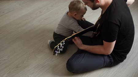 nevinný : Little cute baby listens curiously as his father plays the guitar