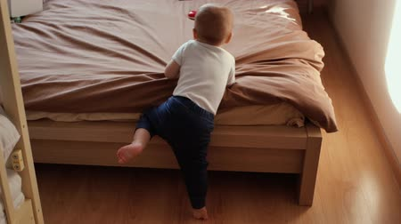 vurguladı : The kid is trying to climb on an adult bed by himself. Cute little boy fails Stok Video