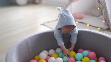 невинный : One happy cute baby throws out multicolored balls out of the pool Funny childrens leisure with ball pits in the play pool, playground