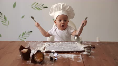 kepçeli : Little cute boy in a chefs cap knocks with cutlery on a wooden table sprinkled with flour. Young cute baby in a chefs cap smiles at the table and licks the flour from a wooden spoon in the kitchen Stok Video