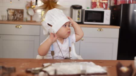 kepçeli : Mom puts the chefs hat on her cute baby, but the child takes it off. The kid is considering the ladle in his hand in the kitchen Stok Video