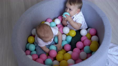 playful infant : Two cute kids playing in a pool of colorful plastic balls. The baby gets to his feet and immediately falls