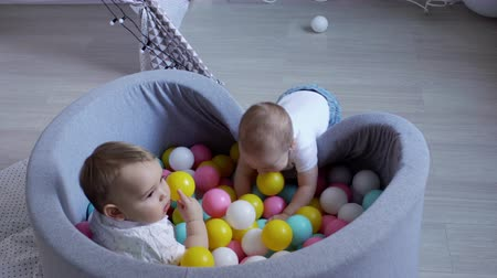 nem sikerül : Cute baby wants to get into a pool of plastic balls to his friend, but he fails. The second baby is quietly watching his actions