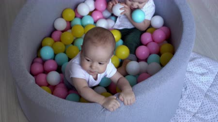 mateřská škola : Two little boys playing in a pool of colored balls. Baby gets to his feet. The second baby sits and tastes a plastic ball