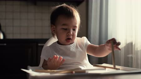 энтузиазм : Little cute baby girl sitting at the table and playing with pencils. The kid is studying pencils with enthusiasm