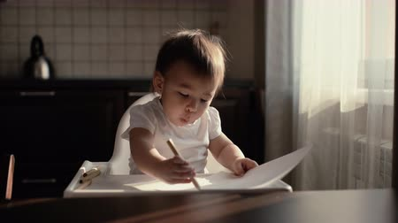nevinný : Little cute baby girl draws a pencil on paper and is pleasantly surprised by her work