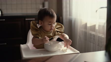 nevinný : Little baby girl in a green bib sits behind a high chair and independently eats a baby porridge from the table with her fingers Dostupné videozáznamy
