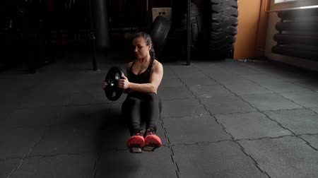 hasi : Strong athletic woman trains abdominal muscles in the crossfit gym in slow motion, holding in hands the weight from the barbell. Sexy beautiful female trains in the gym sitting on the floor