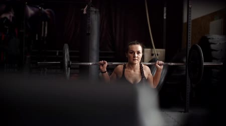 quadriceps : Stranger spies as a beautiful athletic girl performs exercises in the gym in slow motion. Strong muscular woman holds a heavy barbell on her shoulders and performs squat on a knee to train quadriceps Stock Footage