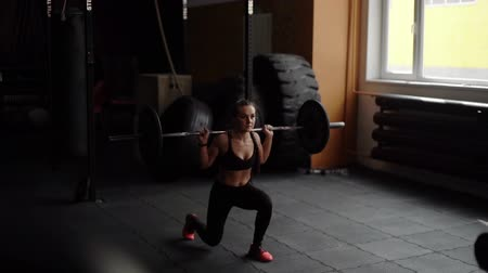 quadriceps : Strong muscular woman holds a heavy barbell on her shoulders and performs a squat on a knee in slow motion. Beautiful athletic girl trains her quadriceps, hips, calf muscles and buttocks in the gym