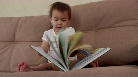 descobrir : Little cute baby girl sits on a soft couch and laughs, turning the pages of a colorful book. Kid shows his finger to parents on the page in the book