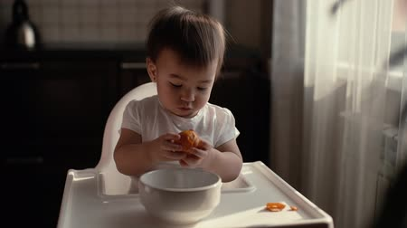 mandarinka : Little cute baby girl in a beautiful green bib sits behind a high childrens chair and independently cleans and eats tangerine Dostupné videozáznamy