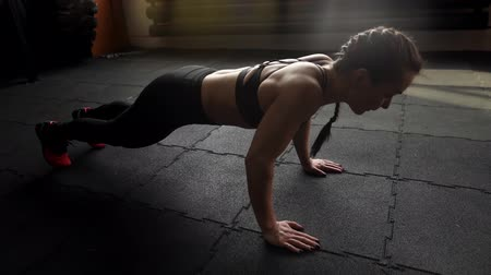 willpower : Athletic beautiful woman doing push-ups on the floor in slow motion in the gym. Sexy muscular girl trains triceps on floor with black mats and repeats 4 times. Camera doesnt move and remains in place
