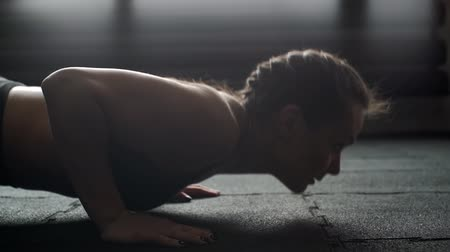 сильный : Athletic beautiful woman close-up on her face doing push-ups in slow motion in the gym. Sexy muscular girl trains triceps on floor with black mats and repeat. Camera doesnt move and remains in place