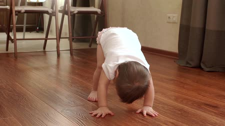 denemek : Little cute baby girl trying to stand up on her own feet in slow motion without any help