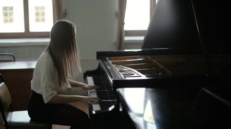 dizgi : Beautiful young woman playing the black piano on the background of the window in slow motion. Pianists face covers her long hair