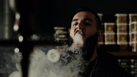 inhaling : Young bearded guy smoking hookah close up and makes rings of smoke at dark room of shisha lounge in slow motion . Round form of a vapor is flying in the air. Hipster exhales smoke from vap nose Stock Footage