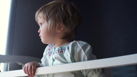 невинный : Little cute baby girl is standing in his crib with his favorite soft toy close up in slow motion. Smiling child looks into the camera, then begins to look out the window