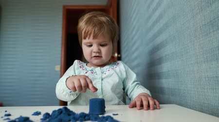kinetik : Little cute baby girl sits at a childs table and plays with kinetic sand on the background of beautiful blue wallpaper in slow motion. Kid thinks for a long time before breaking a kinetic sand figure Stok Video